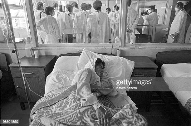 A Kurd woman victim of a mustard gas attack by Saddam Hussein on frontier of IranIraq lies in bed suffering of her wounds while members of...
