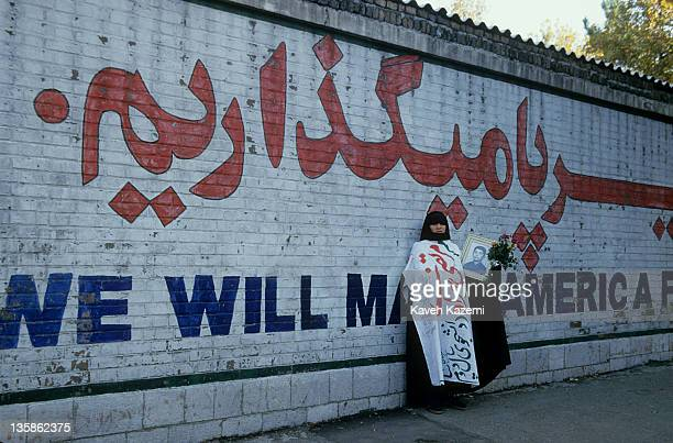 Mother of a young martyr holding a photo of her son killed in the Iran-Iraq War stands outside the embassy and in front of a mural with the slogan...
