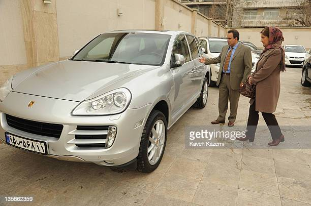 A welltodo couple looking for a new car for the family stand in front of a brand new Porsche Cayenne in a car showroom in Tehran 11th March 2011