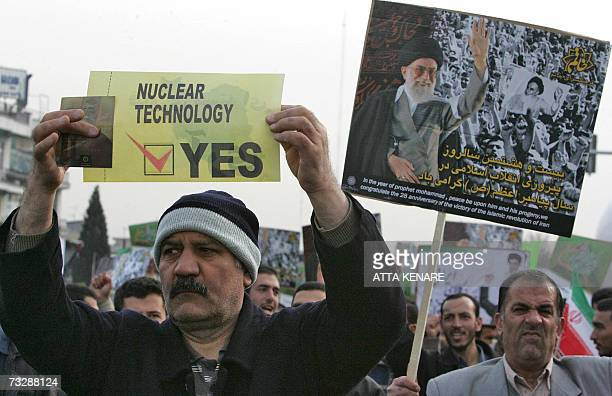 An Iranian man carries a placard in support of nuclear technology as another waves a portrait of Iran's supreme leader Ayatollah Ali Khamenei during...