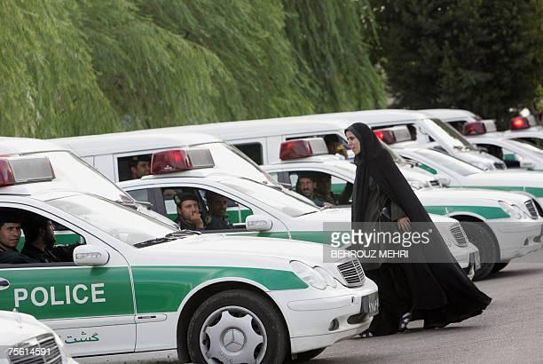 An Iranian policewoman walks between police vehicles preparing to start a crackdown to enforce Islamic dress code in Tehran 23 July 2007 Iran on...
