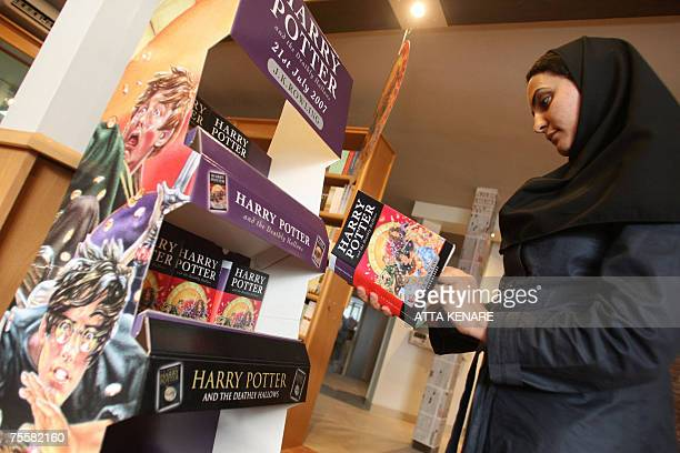 An Iranian woman reads a copy of Harry Potter And The Deathly Hallows in front of a special stand at a bookstore in Tehran 21 July 2007 Harry Potter...