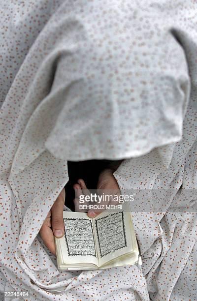 An Iranian woman reads the holy Koran before the start of the Eid alFitr prayers at Tehran's Imam Khomeini Mosalla 24 October 2006 Muslims celebrated...