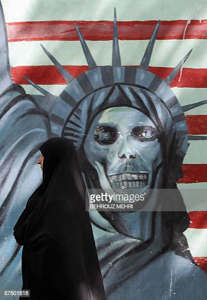 An Iranian woman walks past an antiUS graffiti depicting the Statue of Liberty on the wall of the former US embassy in Tehran 01 May 2006 The United...