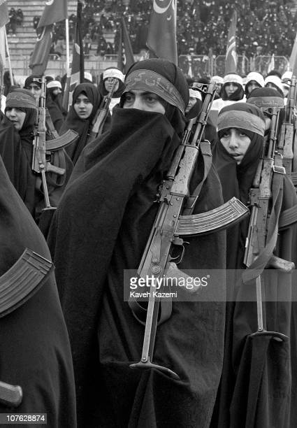 Basiji women in black chador march while carrying AK47 assault rifles in a Tehran rally 12th February 1987 towards the end of the eight year long...