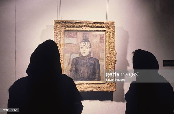 Female visitors fully covered in black Islamic uniforms viewing art piece by Toulouse Lautrec's famous painting 'Filles de Montmartre' in the...