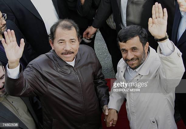 Iranian President Mahmoud Ahmadinejad and his Nicaraguan counterpart Daniel Ortega wave upon Ortega's arrival at Mehrabad airport in Tehran 10 June...