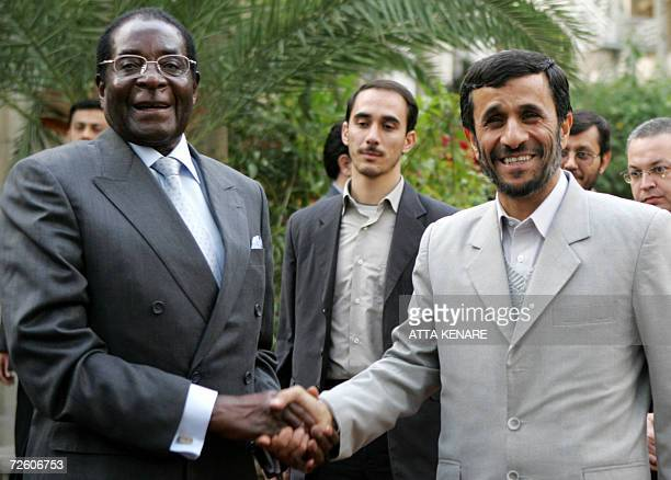 Iranian President Mahmud Ahmadinejad shakes hands with his Zimbabwean counterpart Robert Mugabe in Tehran 20 November 2006 Mugabe is on a fourday...