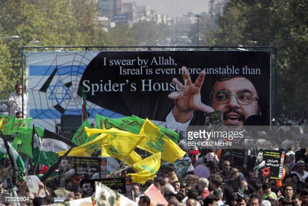 Iranian protestors holding up a huge banner with the picture of Lebanon's Hezbollah leader Hassan Nasrallah and waving yellow flags of the Shiite...