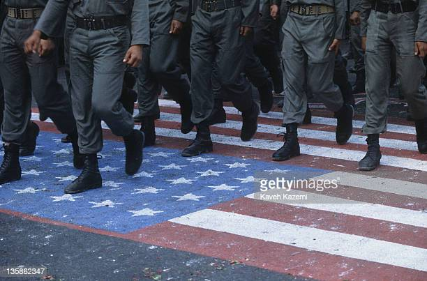 Iranian Revolutionary Guards march on a US flag painted on the tarmac of Azadi square during the anniversary of the revolution in Tehran, 11th...