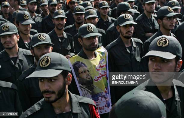 Iranian Revolutionary Guards one of them covering his chest with a portrait of Lebanon's Hezbollah leader Hassan Nasrallah take part in a...