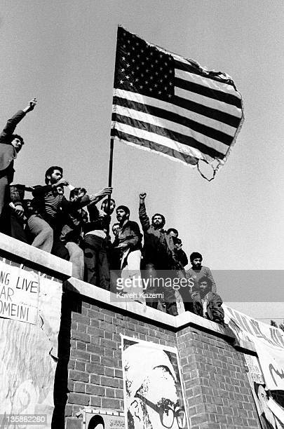 Iranian students following the Imam Khomeini line burn a US flag while standing on the walls of the compound of the American embassy a week after it...