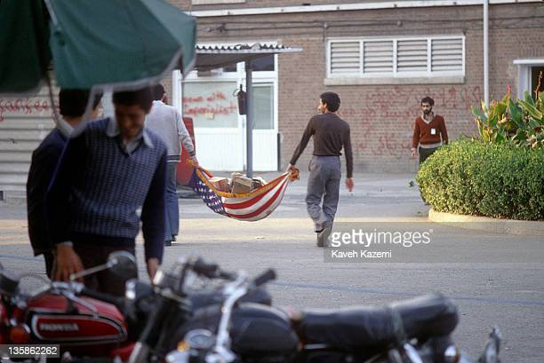 Iranian students following the Imam Khomeini line carry trash in a US flag inside the compound of the American embassy in Tehran 15th November 1979...