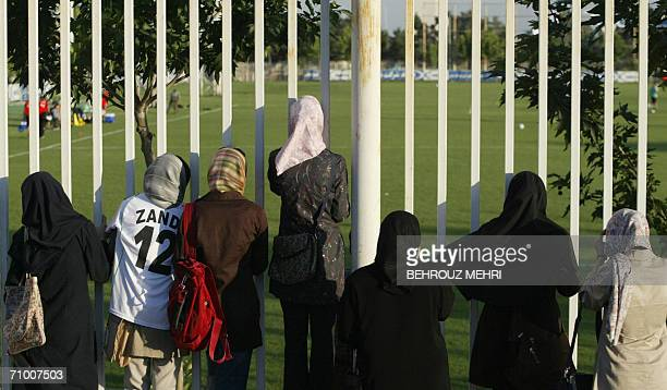 Iranian women watch a training session of Iran's national football team from behind a fence as females were not allowed to enter the stadium at...