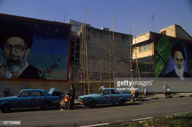 People wait for shuttle taxis under murals of Ayatollah Ali Khamenei and Ayatollah Khomeini in a north Tehran street 1st April 1999
