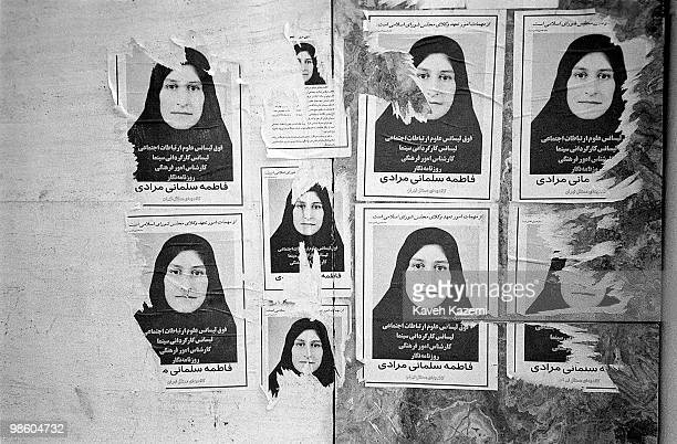 Posters of a woman running for a seat in parliament are torn off the wall they were pasted on in Tehran