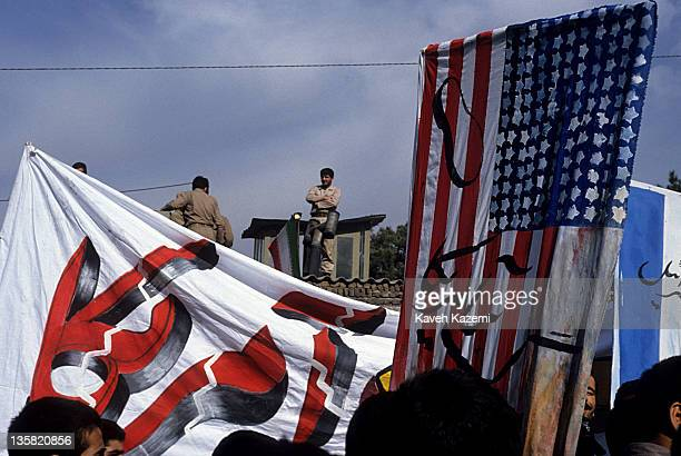 Revolutionary Guards stand guard on top of the US Embassy walls during the anniversary of its occupation, 4th November 1996. Demonstrators carry U.S....