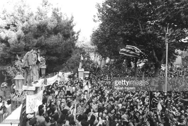 Standing on the walls of the compound Iranian students following the Imam Khomeini line throw a US flag into the crowds gathering outside the...
