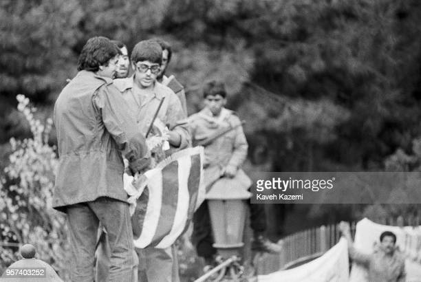 Standing on the walls of the compound, Iranian students following the Imam Khomeini line prepare to throw a US flag into the crowds gathering outside...