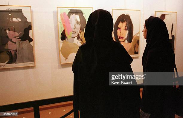 Two female visitors fully covered in Islamic black uniform viewing The Mick Jagger pieces by Andy Warhol on display at the Tehran Museum of...