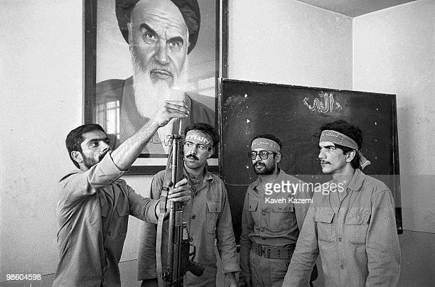 Under watchful eyes of Ayatollah Khomeini an instructor shows a group of Basiji men in a Tehran factory how to use fire arms as part of mass...