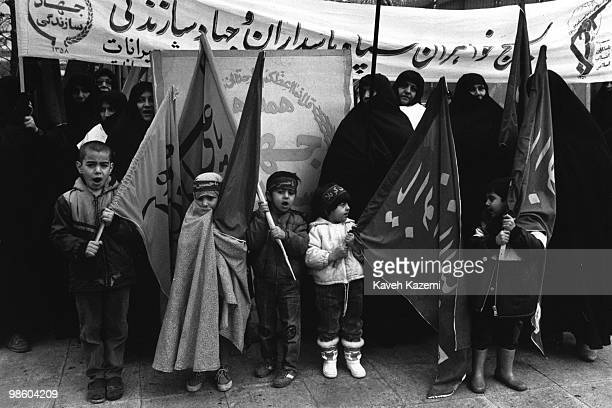 Young kids hold religious banners during a Basij assembly in Shiroudi stadium in Tehran, 4th February 1986.