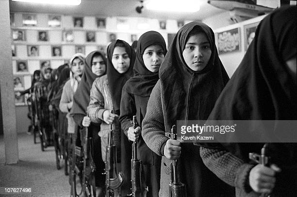 Young schoolgirls in Islamic veils go through arms training as a Basijis while holding AK47 automatic assault rifles and standing in front of...