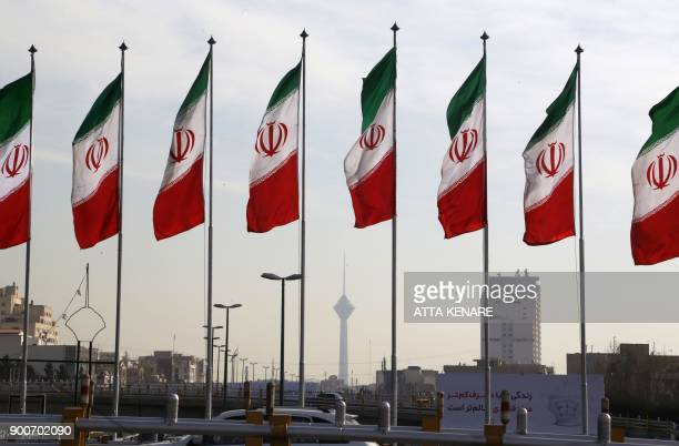 Tehran's landmark Milad Tower is seen through a row of national flags in the centre of the Iranian capital on January 3 2018 Tens of thousands were...