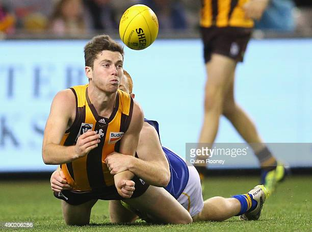 Teia Miles of the Hawks handballs whilst being tackled by Anthony Anastasio of the Seagulls during the VFL Grand Final match between Williamstown and...