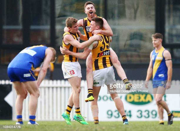 Teia Miles of the Hawks jumps on Oliver Hanrahan and Mitchell Lewis as they celebrate the win during the VFL Preliminary Final match between...