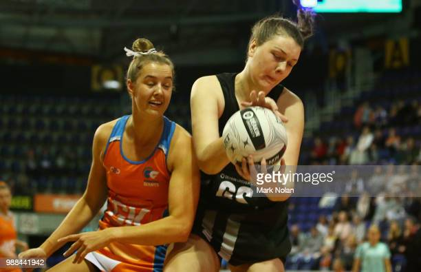 Teigan O'Shannassy of the Giants and Jane Cook of the Magpies contest possession during the Australian Netball League grand final between the...