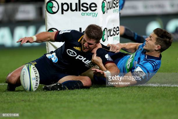 Teihorangi Walden of the Highlanders dives over to score a try in the tackle of Matt Duffie of the Blues during the round two Super Rugby match...