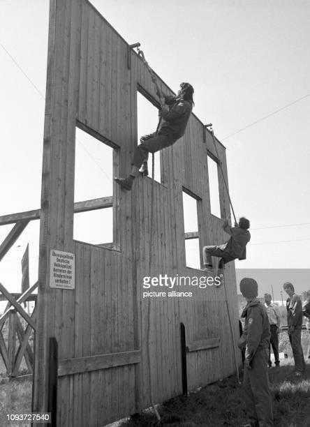 Teilnehmer der II. Kreiswehrspartakiade Buna der GST am überwinden beim Militärischen Mehrkampf eine Häuserwand. - Die Gesellschaft für Sport und...