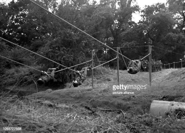 Teilnehmer der II. Wehrspartakiade der GST im Jahre 1975 in Magdeburg hangeln sich beim Hindernislauf über einen Graben. - Die Gesellschaft für Sport...