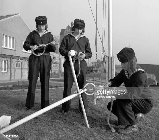 Teilnehmer eines Seesportlehrgangs üben auf dem Gelände des GSTZentrum Seeburg im früheren Bezirk Halle an einem Anker das Anfertigen von Knoten...