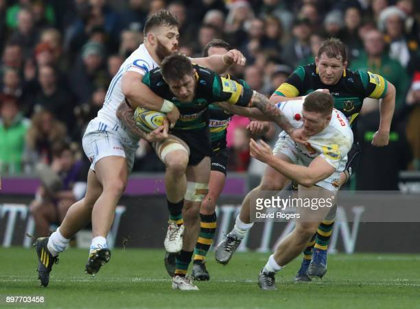 Teimana Harrison of Northampton is tackled by Luke CowanDickie and Sam Simmonds during the Aviva Premiership match between Northampton Saints and...