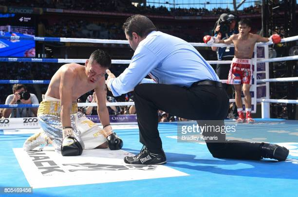 Teiru Kinoshita of Japan is counted down by the referee as Jerwin Ancajas of the Philippines looks on during their IBF World Junior Bantamweight...
