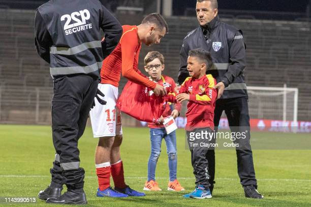April 20: Teji Savanier of Nimes gives a crying boy his shirt and then escorts him back to the stands after he came onto the field after the Nimes V...