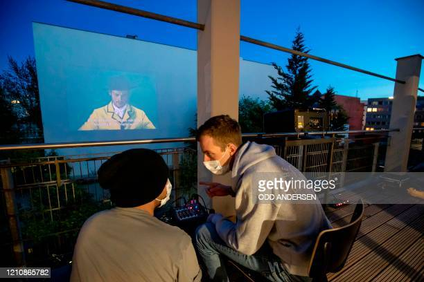 Tek Chung and Nikos Perimenis from Window Flicks set up to start projecting the movie Loving Vincent on the wall of a building in Berlin's Kreuzberg...