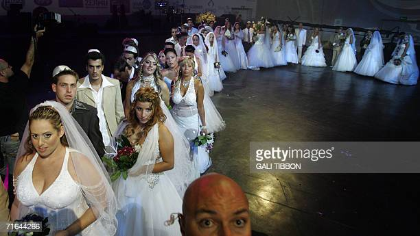 Over 30 Israeli couples from northern Israel wait to be married during a mass wedding ceremony 14 August 2006 in TelAviv More than 70 weddings have...