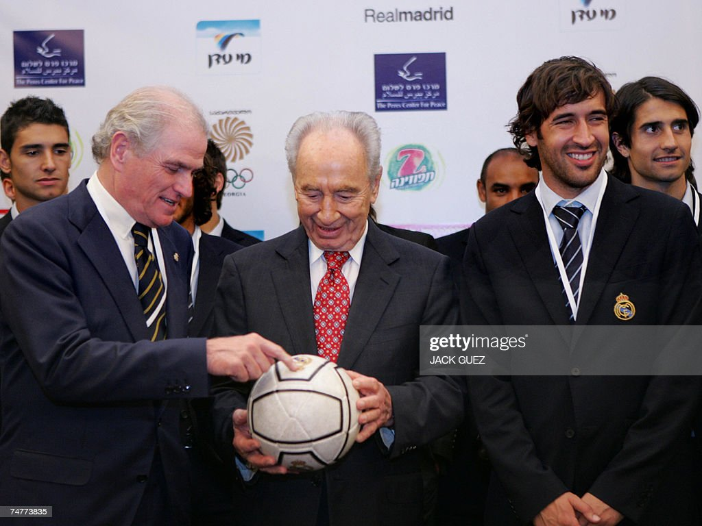 Spanish Real Madrid soccer team President Ramon Calderon (L) gives a football to newly elected Israeli President Shimon Peres as he stands next to Real Madrid's team captain Raul Bravo in Tel Aviv prior to tonight's 'Peace Match' hosted by the Peres Center for Peace, 19 June 2007. The Peres Center's 'Peace Team', comprised of both Palestinian and Israeli players will play against Real Madrid tonight at the Ramat Gan Stadium, near Tel Aviv.
