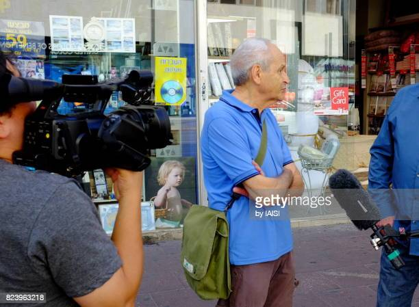 Tel Aviv street scene, interview of a senior citizen