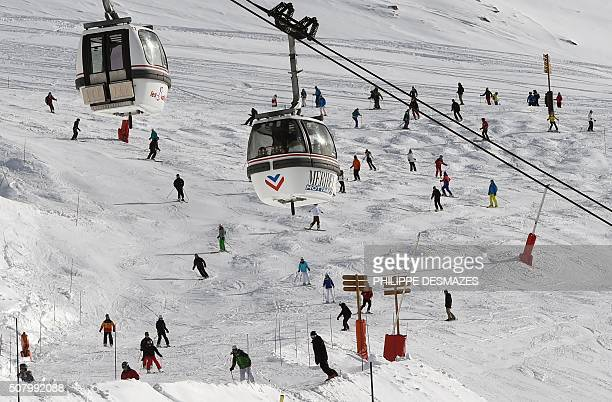 Telecabins are pictured above people skiing down a slope on February 2 2016 in the French ski resort of Meribel at the junction with Les Menuires and...