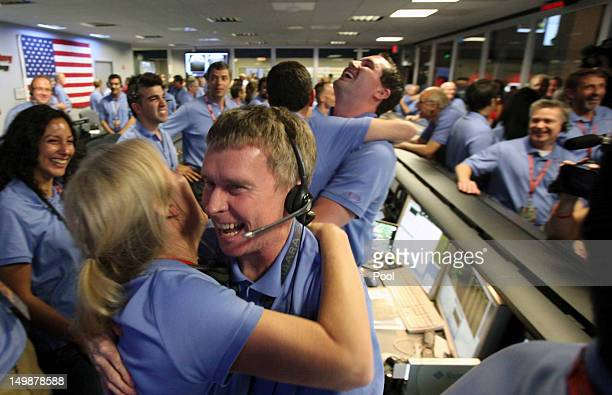 Telecom engineer Peter Ilott hugs a colleague celebrating a successful landing inside the Spaceflight Operations Facility for NASA's Mars Science...