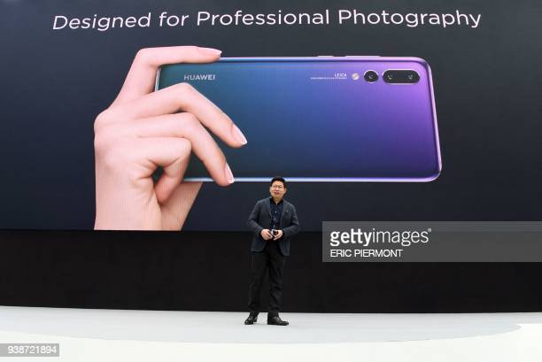 Telecom equipment company Huawei CEO Richard Yu presents the new P20 smartphone in Paris on March 27 2018 / AFP PHOTO / ERIC PIERMONT