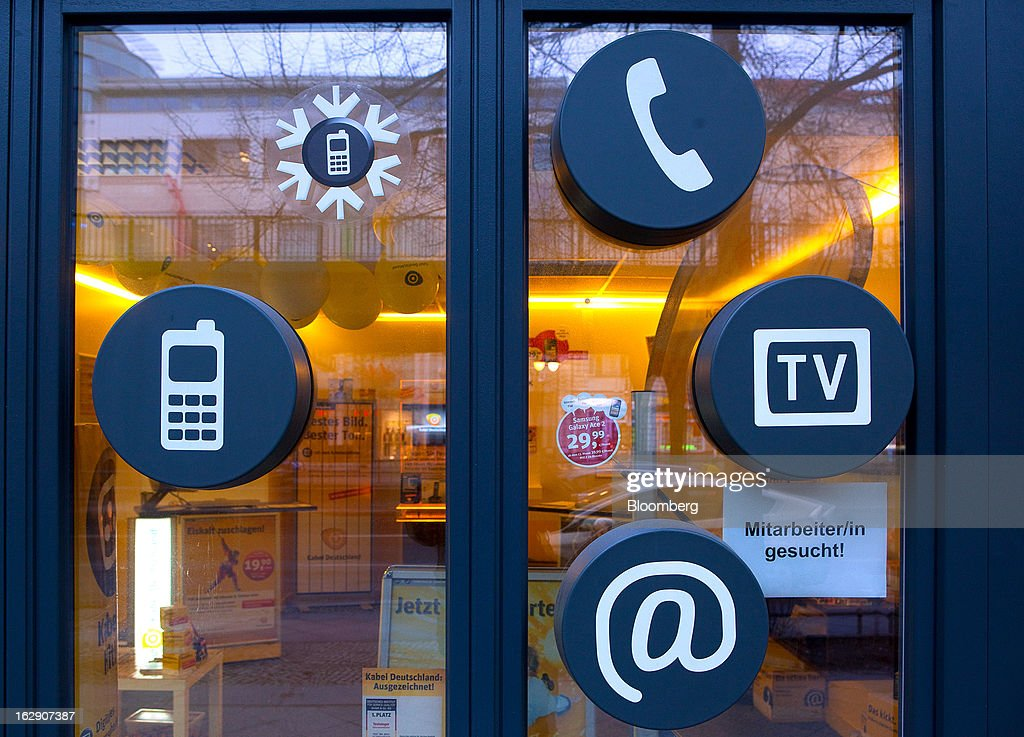 Telecommunication symbols for a phone, television and mobile handset are seen on the window display of a Kabel Deutschland store, operated by Kabel Deutschland Holding AG the German cable operator in Berlin, Germany, on Friday, March 1, 2013. Vodafone Group Plc has put on hold plans to approach Kabel Deutschland Holding AG about a takeover bid after leaks of a potential offer complicated internal discussions, according to three people familiar with the matter. Photographer: Krisztian Bocsi/Bloomberg via Getty Images