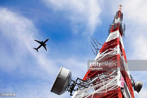 Telecommunication Tower on blue sky and clouds with plane