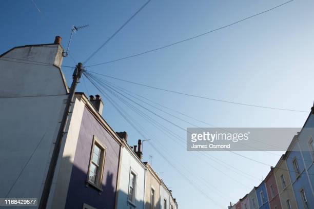 telegraph pole and wires connected to a multicolour row of terraced houses. - in a row stock pictures, royalty-free photos & images