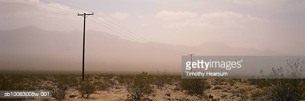 telegraph poles and lines in desert with sand storm in background - timothy hearsum ストックフォトと画像