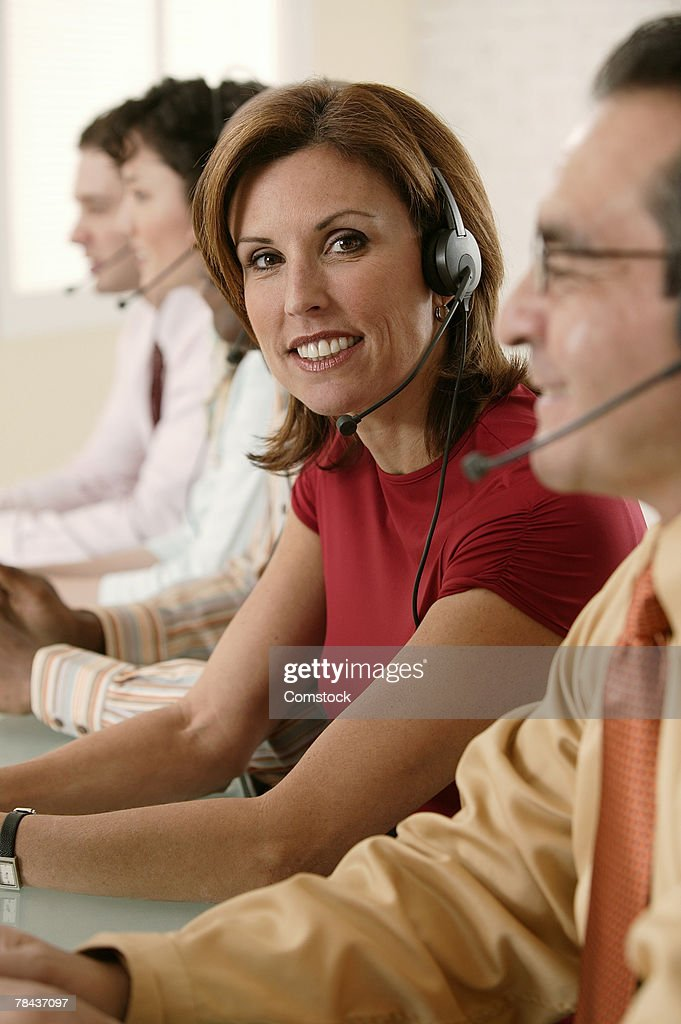 Telemarketer posing among co-workers : Stockfoto